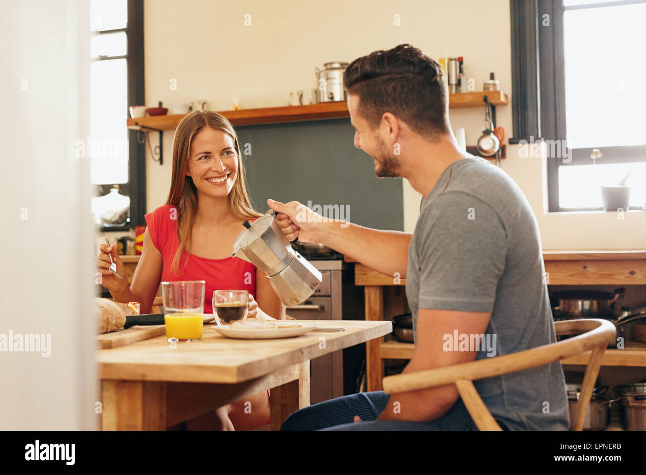 Indoor shot of young man serving coffee to his girlfriend having breakfast in kitchen at home. Smiling young couple - Stock Image