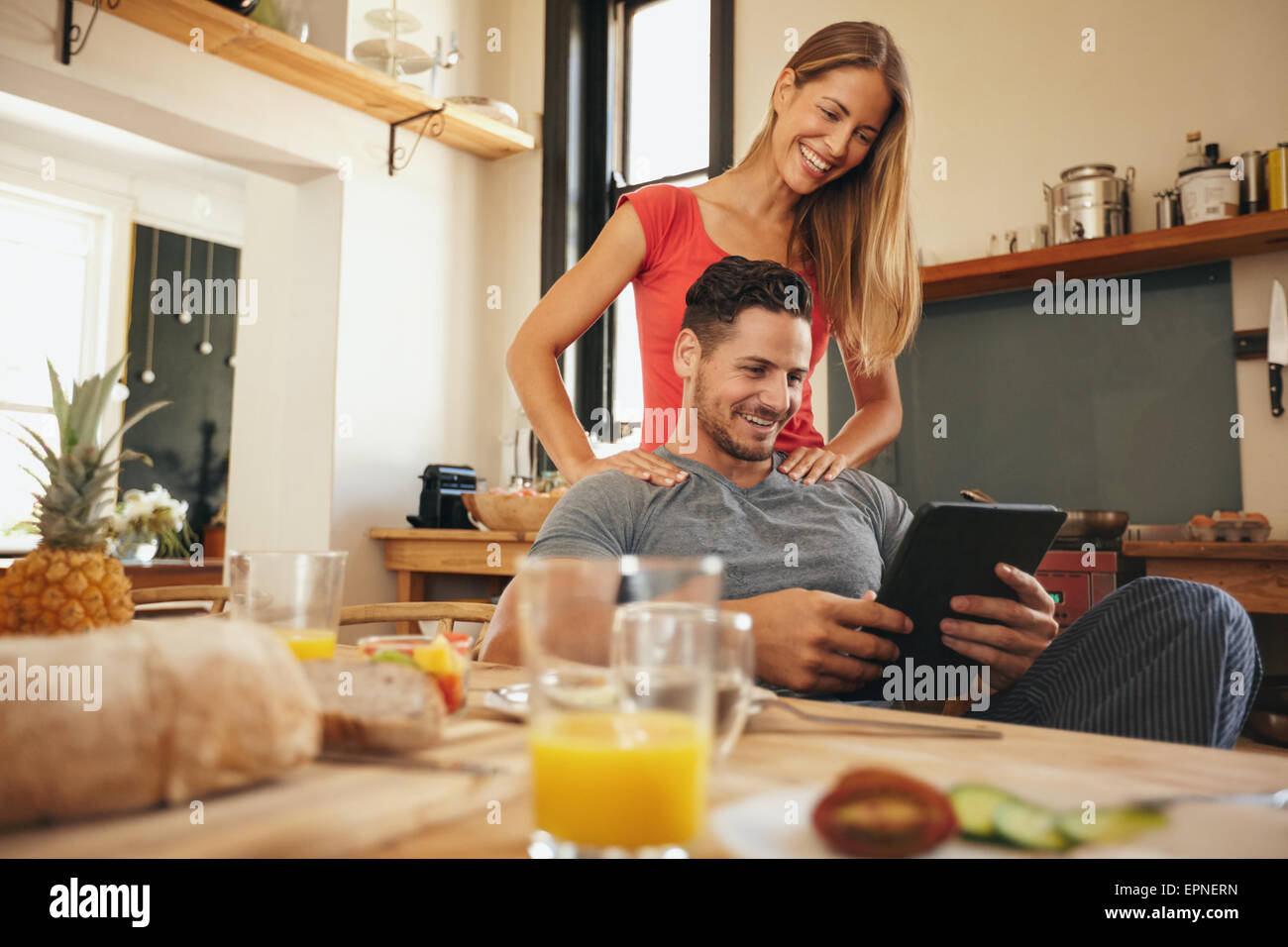 Shot of happy young man and woman using digital tablet in morning. Couple using touchpad in kitchen smiling. - Stock Image