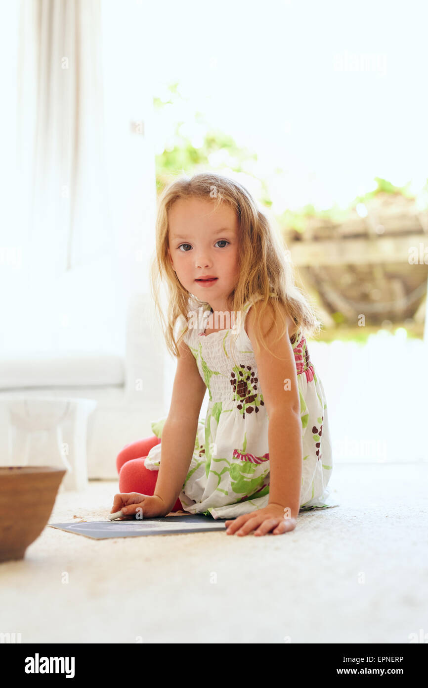 Portrait of cute little girl drawing while sitting on floor at home looking at camera. Elementary age young girl - Stock Image