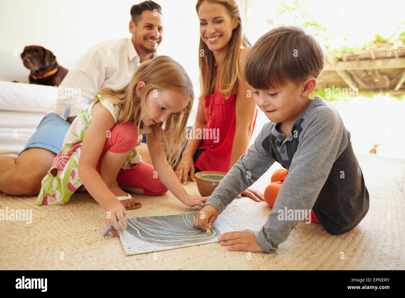 Little boy and girl drawing with chalk colors while sitting on floor. Children drawing with their parents in living - Stock Image