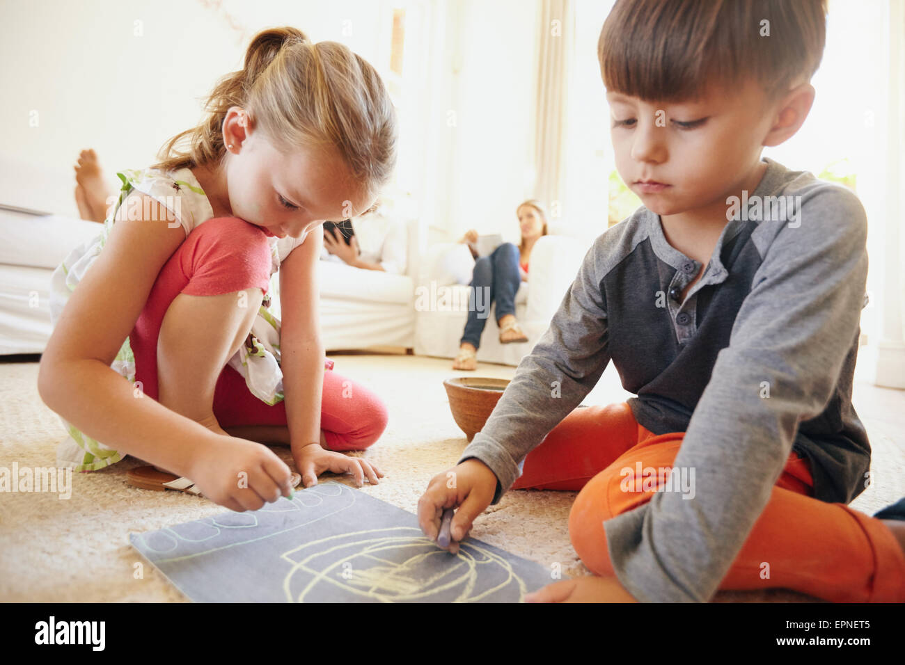 Little siblings drawing a picture with chalk colors. Cute children sitting on floor with parents in background in - Stock Image