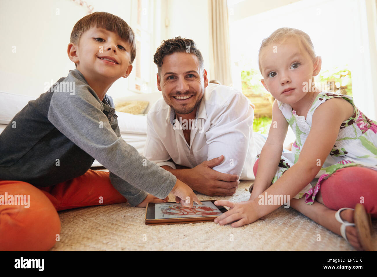 Family sitting on floor using digital tablet looking at camera smiling. Father with son and daughter playing with - Stock Image