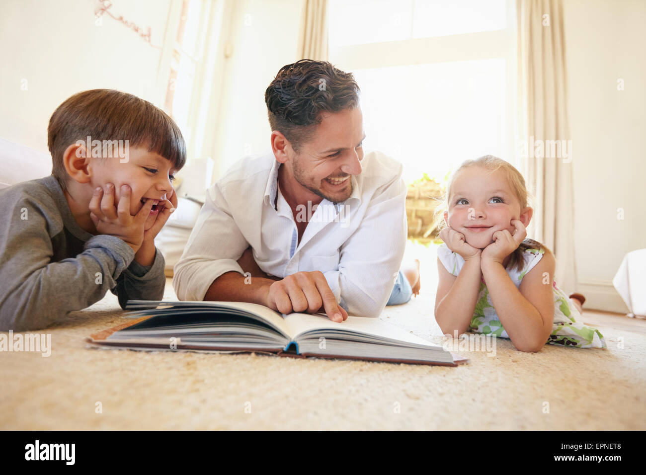 Portrait of happy young family of three lying on floor with a book. Father with two kids reading a story book in Stock Photo