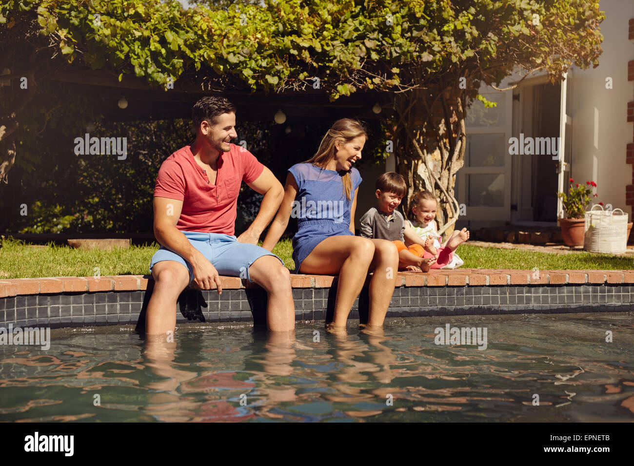 Happy young couple sitting on the edge of swimming pool with their kids enjoying a hot summer day near pool. Couple's - Stock Image
