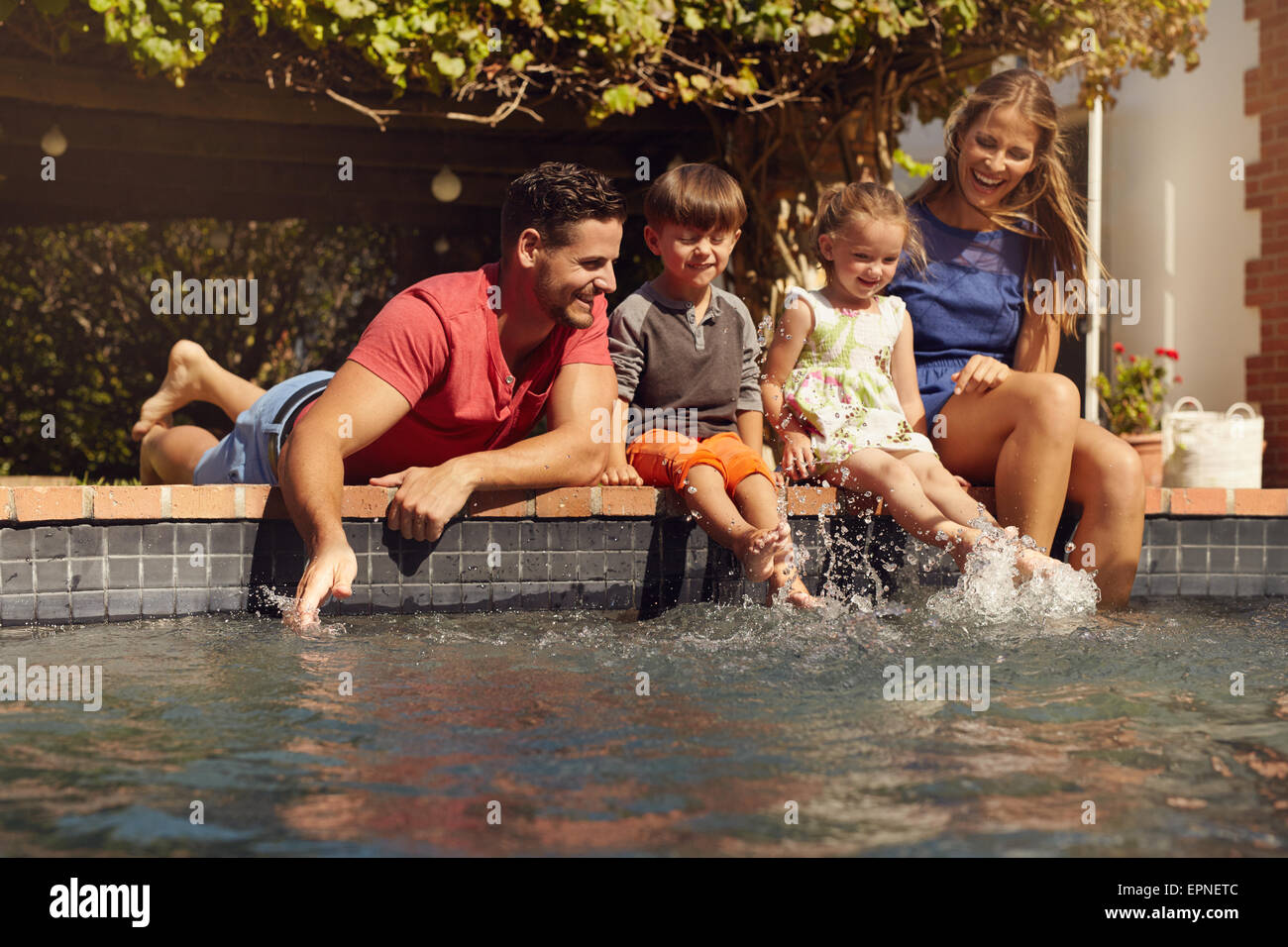Caucasian family having fun by their swimming pool. Happy young family splashing water with hands and legs while - Stock Image