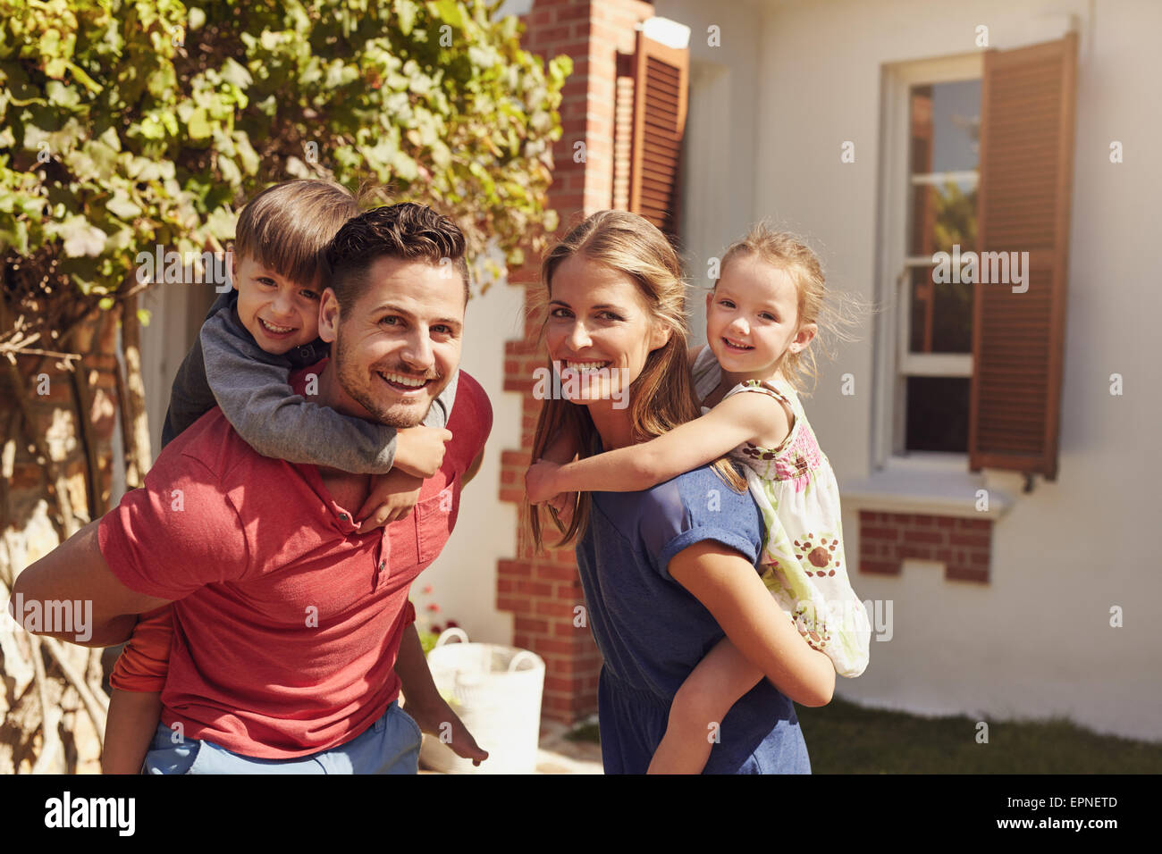 Happy father and mother looking at camera while piggybacking their son and daughter. Happy young family of four - Stock Image