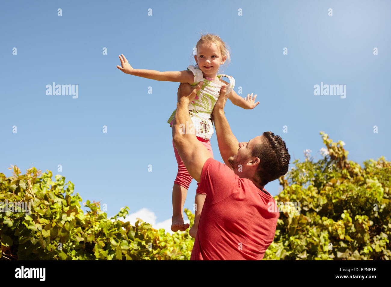 Little girl pretending to be a airplane as her father lifts her in the air. Father holding his daughter up high - Stock Image