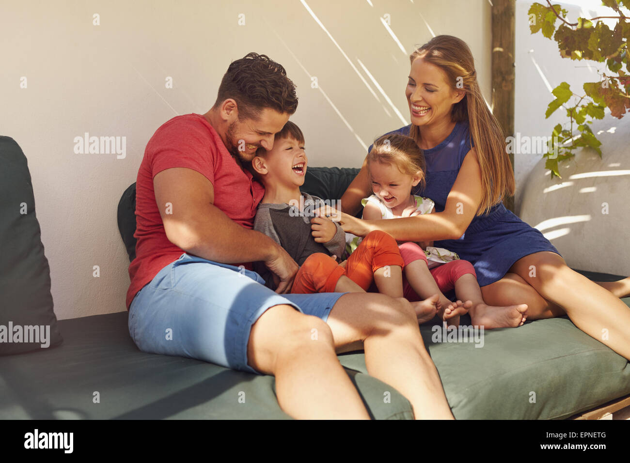 Shot of happy family of four in their backyard having fun, sitting on couch playing. Parents playing with kids laughing - Stock Image