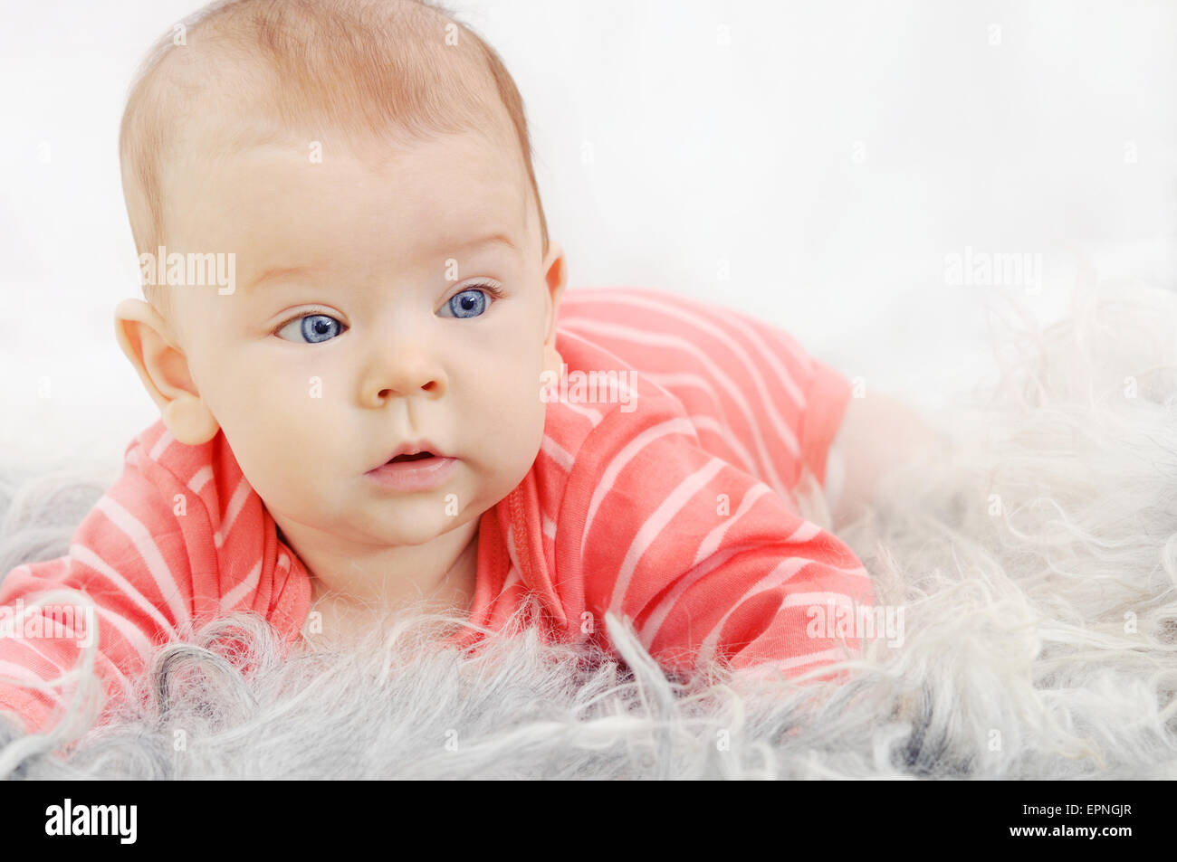 adorable cute little girl with big blue eyes and wide smile playing on the white sofa - Stock Image