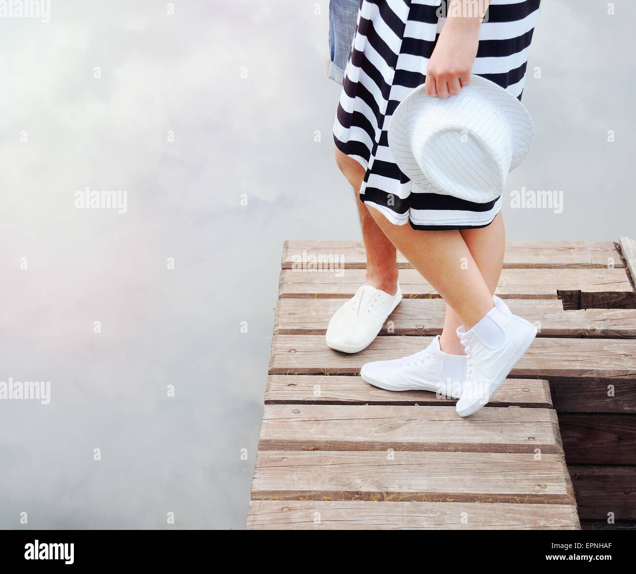 couple kissing on the pier near lake in hot summer day, summer concept - Stock Image