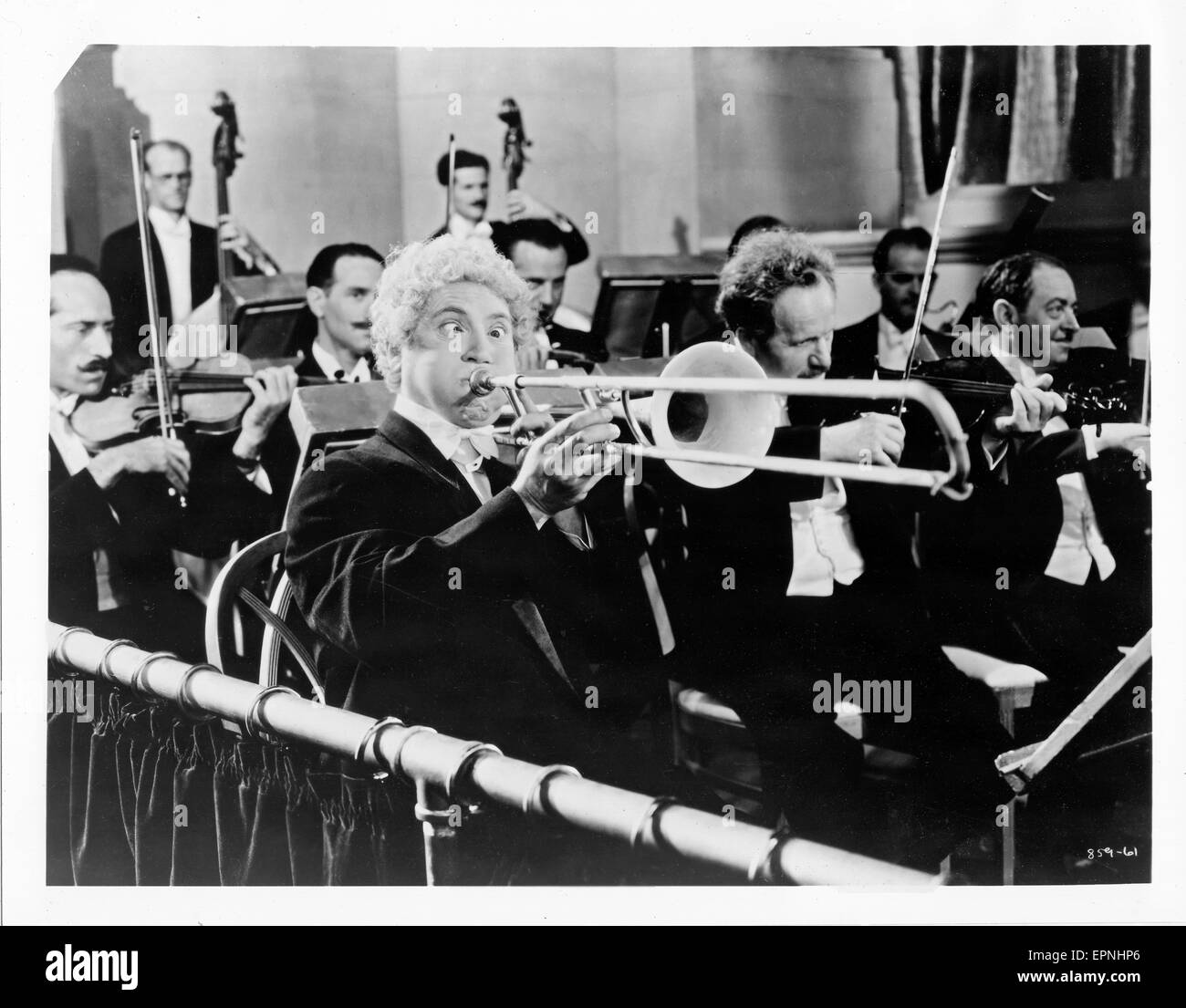 Harpo Marx playing the trombone in a scene from the 1935 film 'A NIght at the OPera' - Stock Image