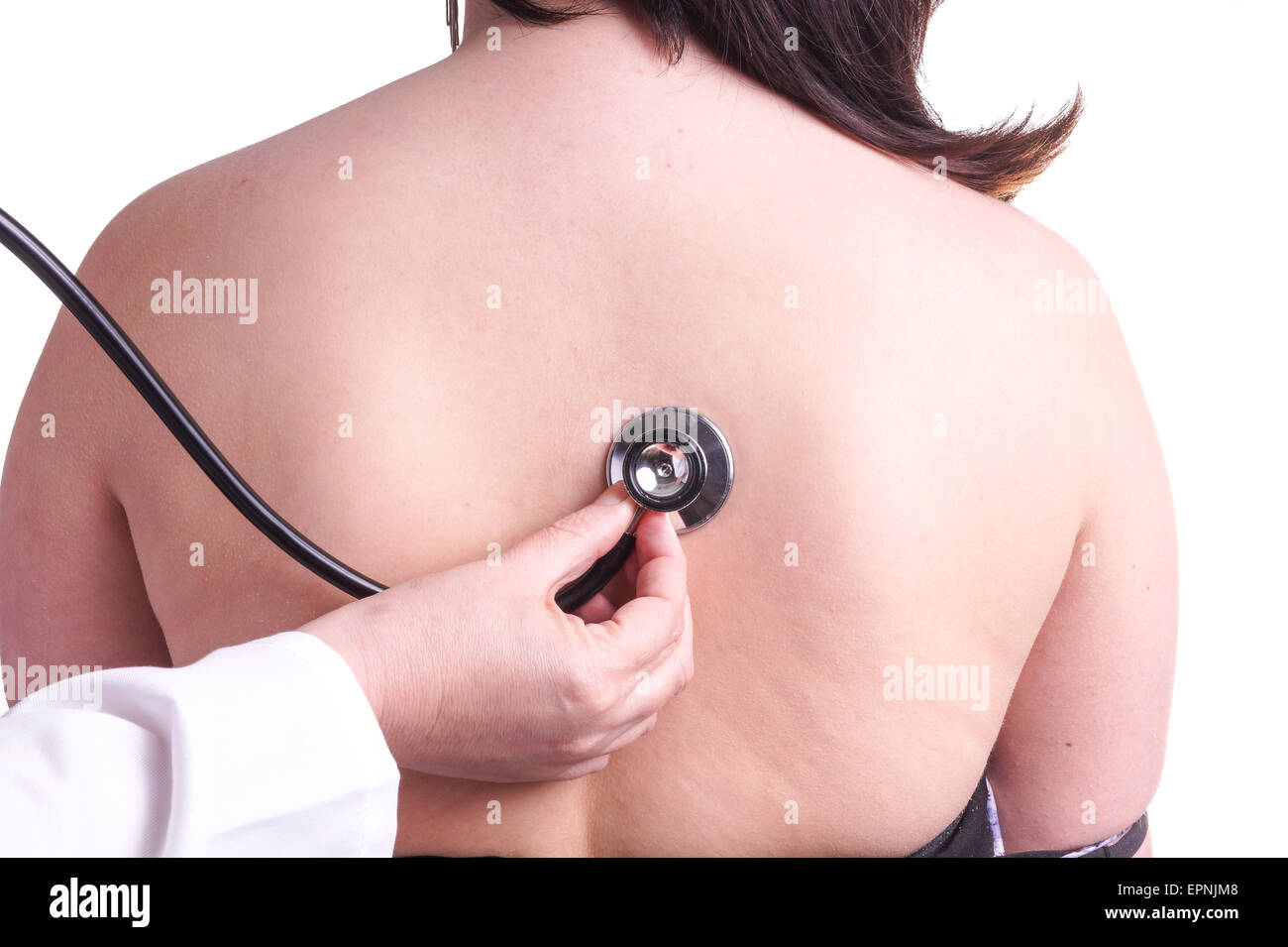 Young woman being investigated for pneumonia by her family doctor . Isolated on white. The picture shows her bare Stock Photo