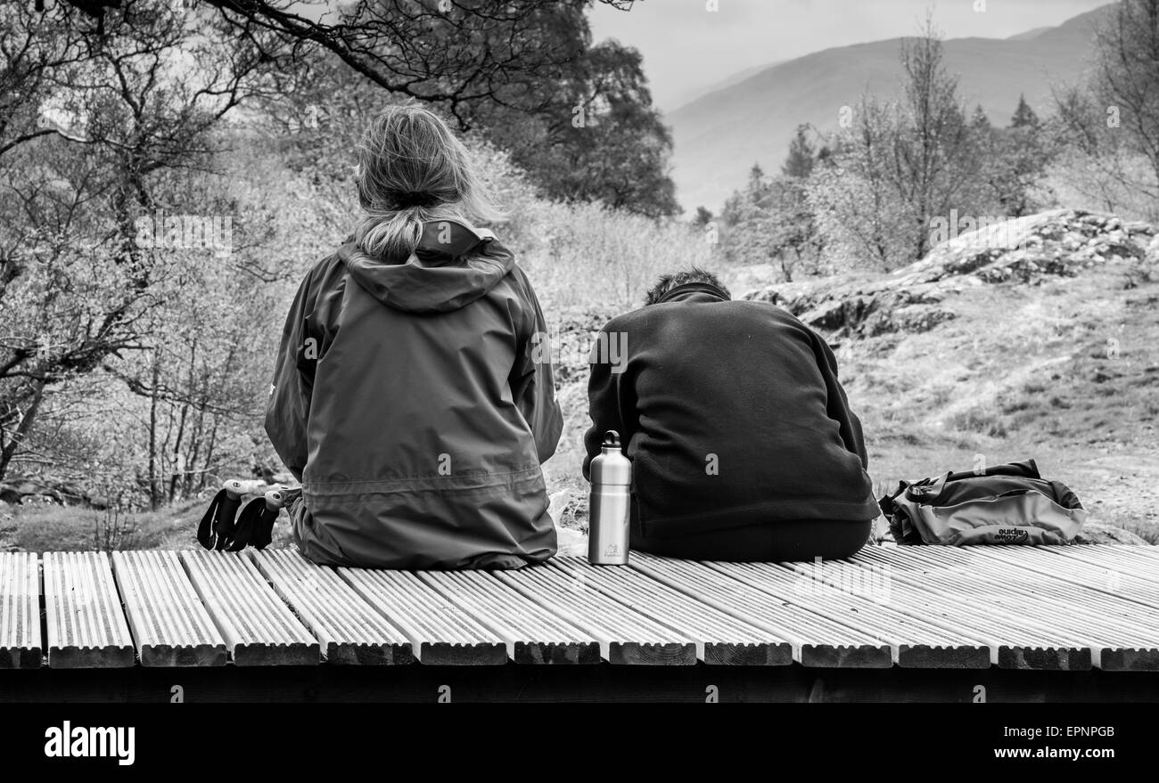 Two hikers picnicking on bridge spanning the Upper Falls of Aira Beck, above Aria Force, near Ullswater, Lake District, - Stock Image