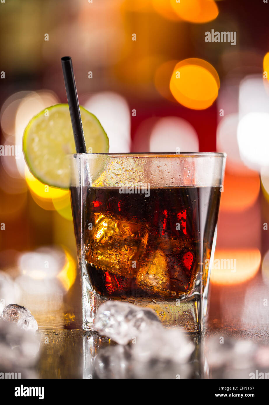 Glass of cola drink on bar counter with ice cubes - Stock Image