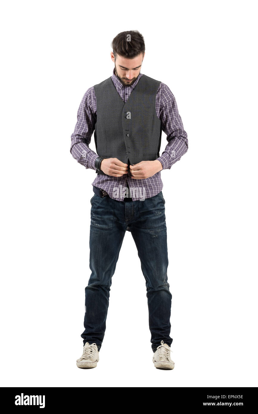 Young bearded man buttoning waistcoat looking down. Full body length portrait isolated over white background. - Stock Image