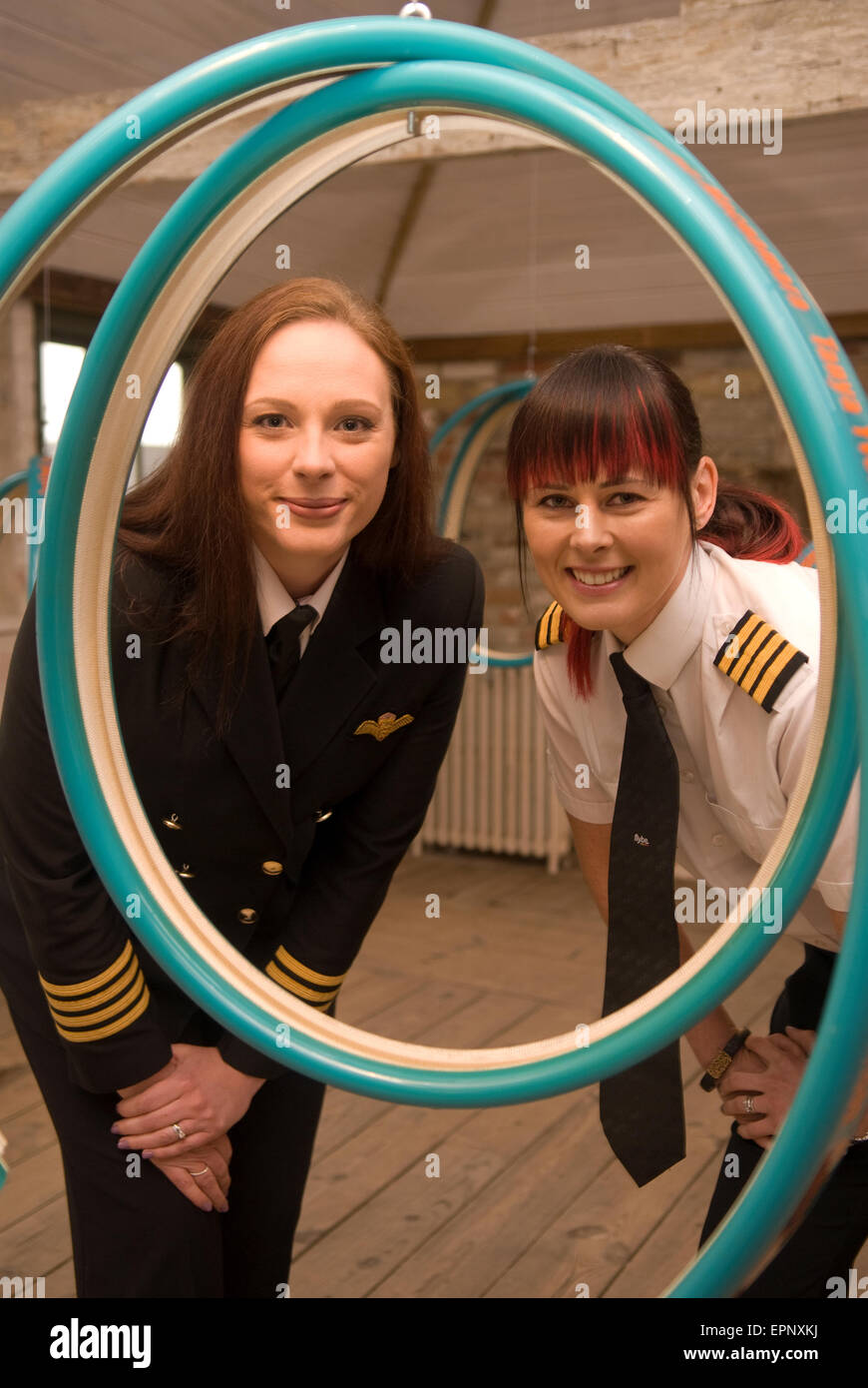 Two female airline pilots looking through artist Ros Burgin's 12-piece installation 'Skylines' intended to celebrate Stock Photo