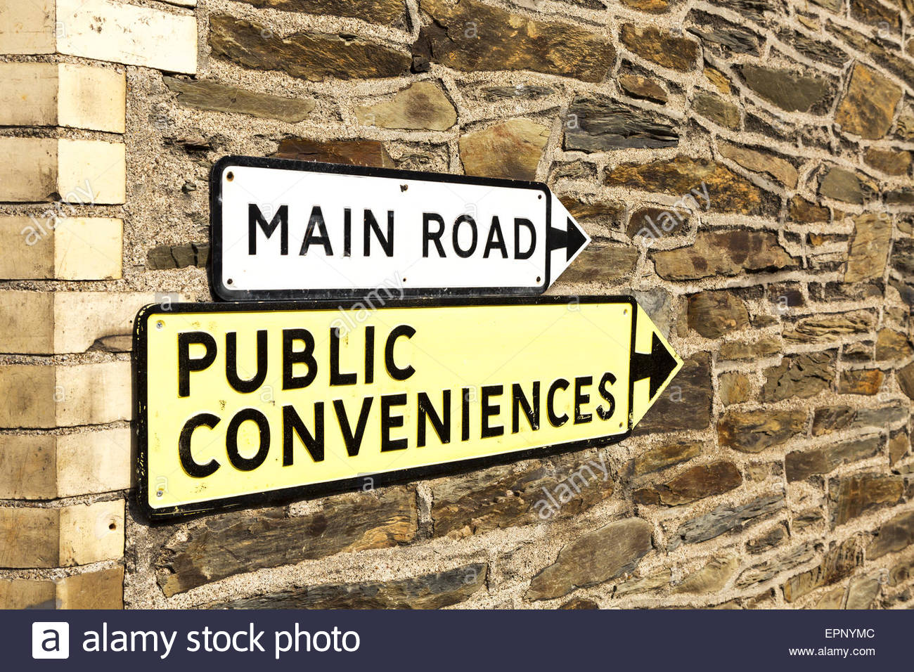 Main Road and Public Conveniences signs with pointing arrows on a stone wall. - Stock Image