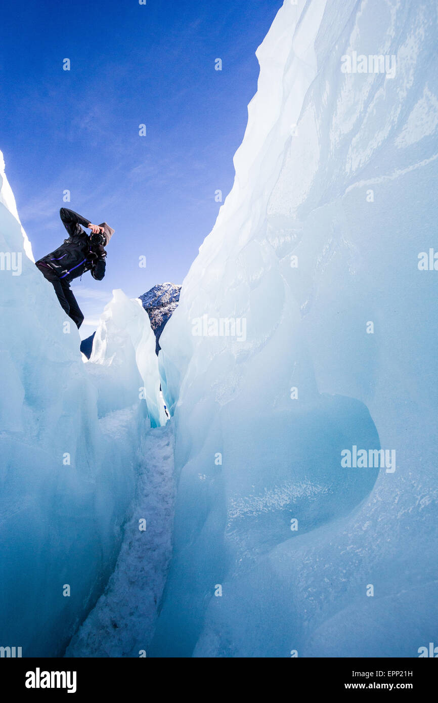 A woman pointing a camera into a deep crevasse in the ice of Fox glacier in the Southern Alps of New Zealand - Stock Image