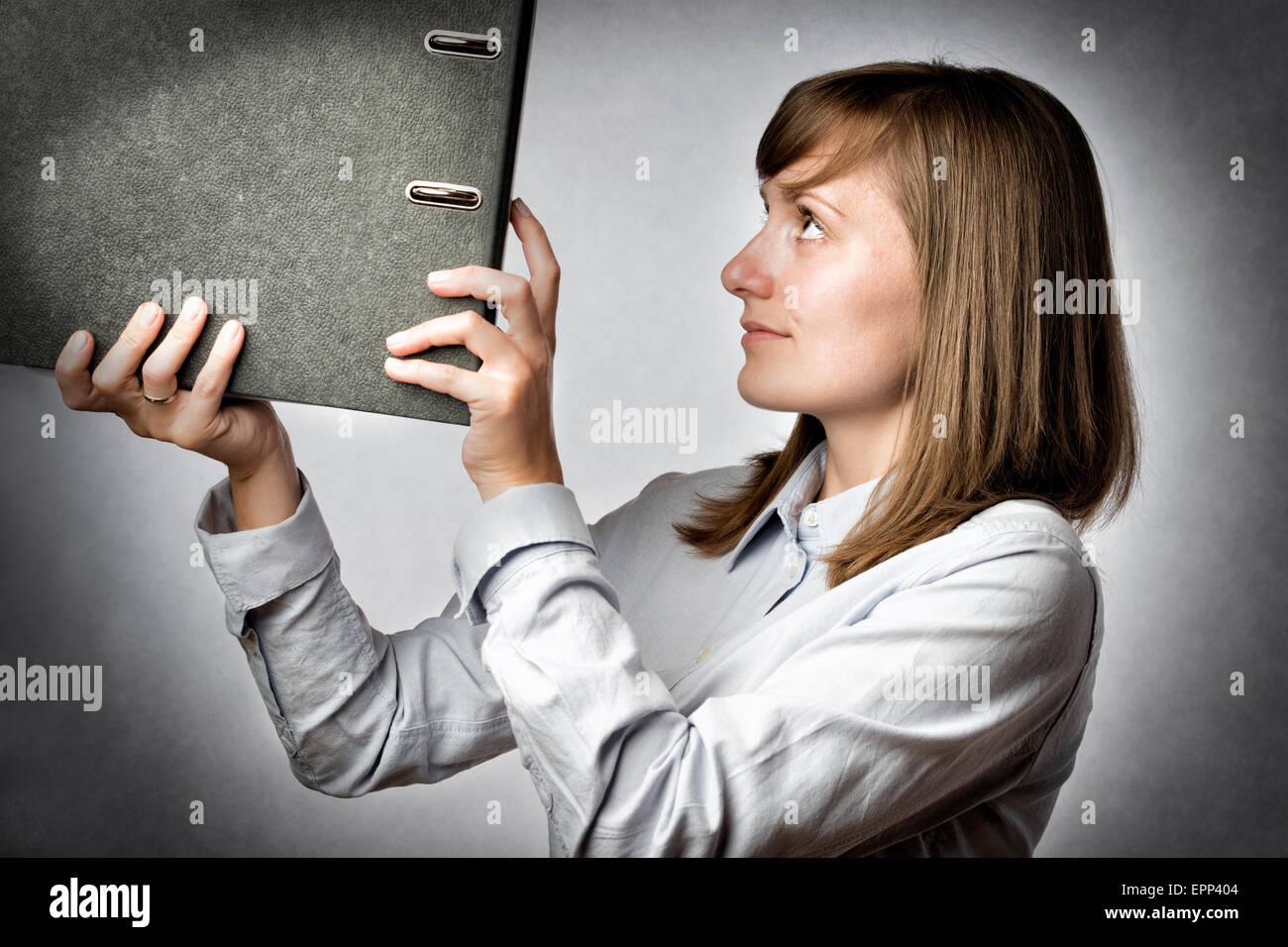 Female office worker puts a folder in a shelf - Stock Image