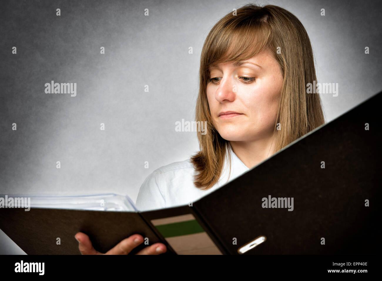 Female office worker is reading in a folder - Stock Image