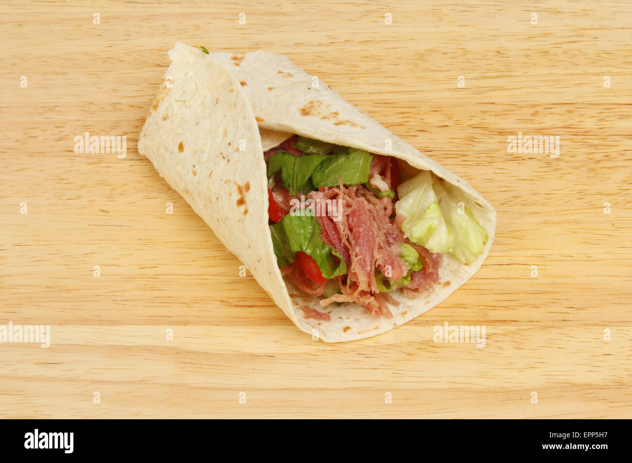 Pulled pork and salad bread wrap on a wooden board - Stock Image