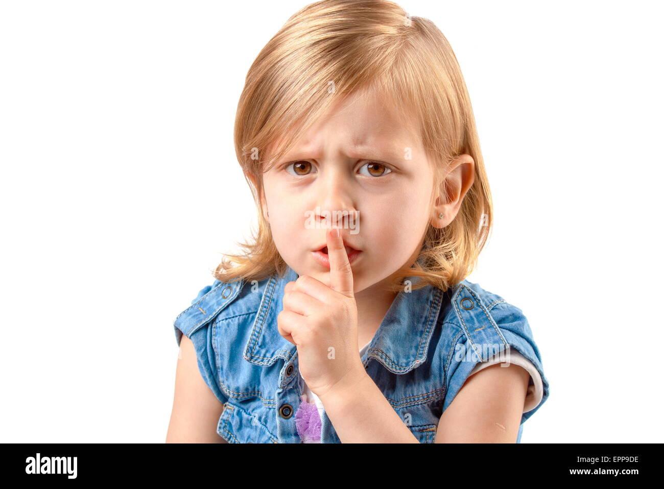 Portrait of little girl making hush sign - Stock Image
