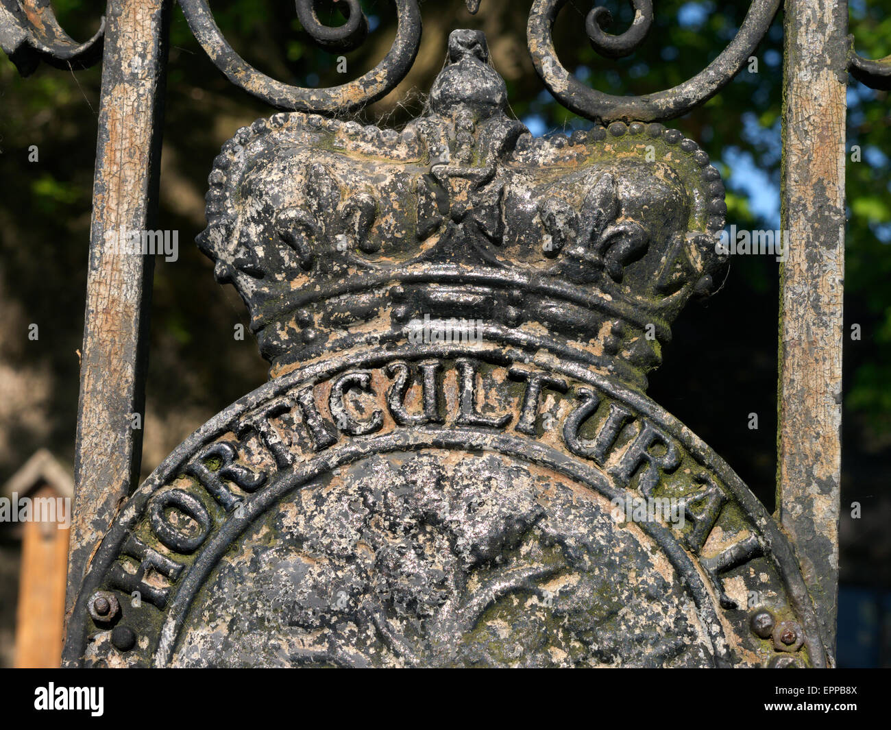 Close-up on weathered Royal Horticultural Society (RHS) metal plaque emblem on entrance gates with garden shed behind Stock Photo