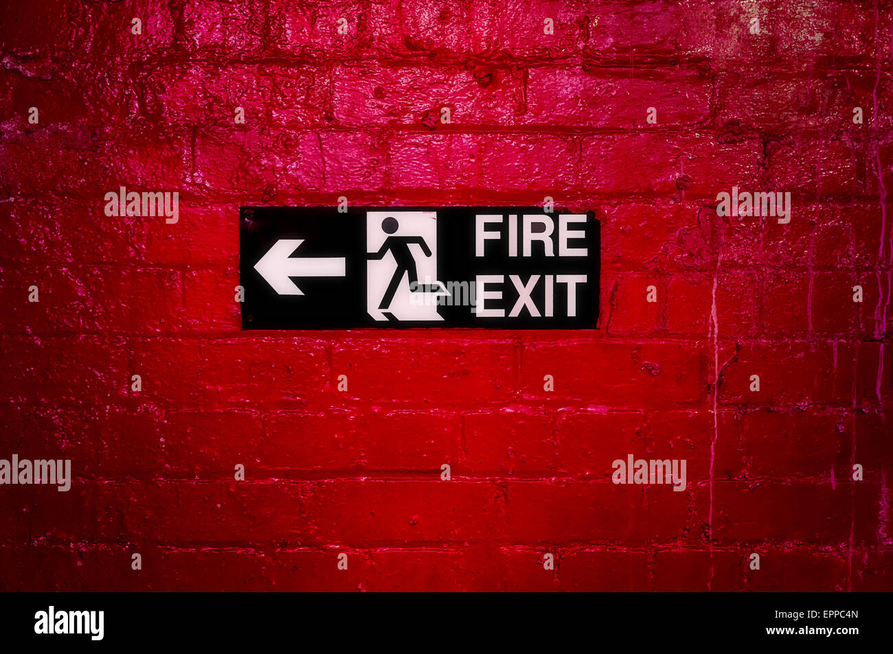 Sign Informing about the fire escape hung on a brick wall painted red. Stock Photo