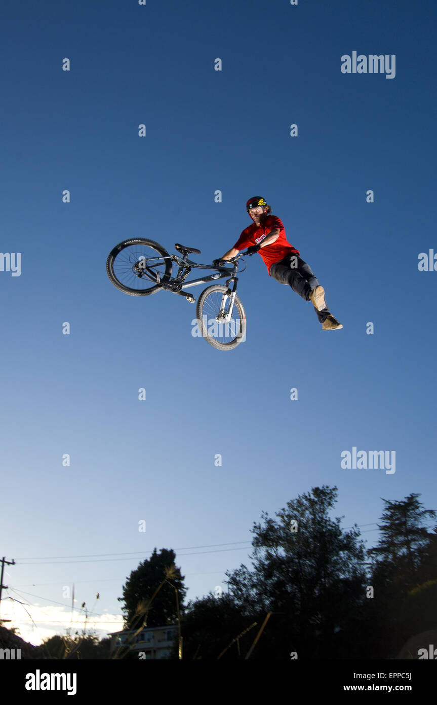 Man dirt jumping on his mountain bike in Aptos, California while filming for New World Disorder - Stock Image