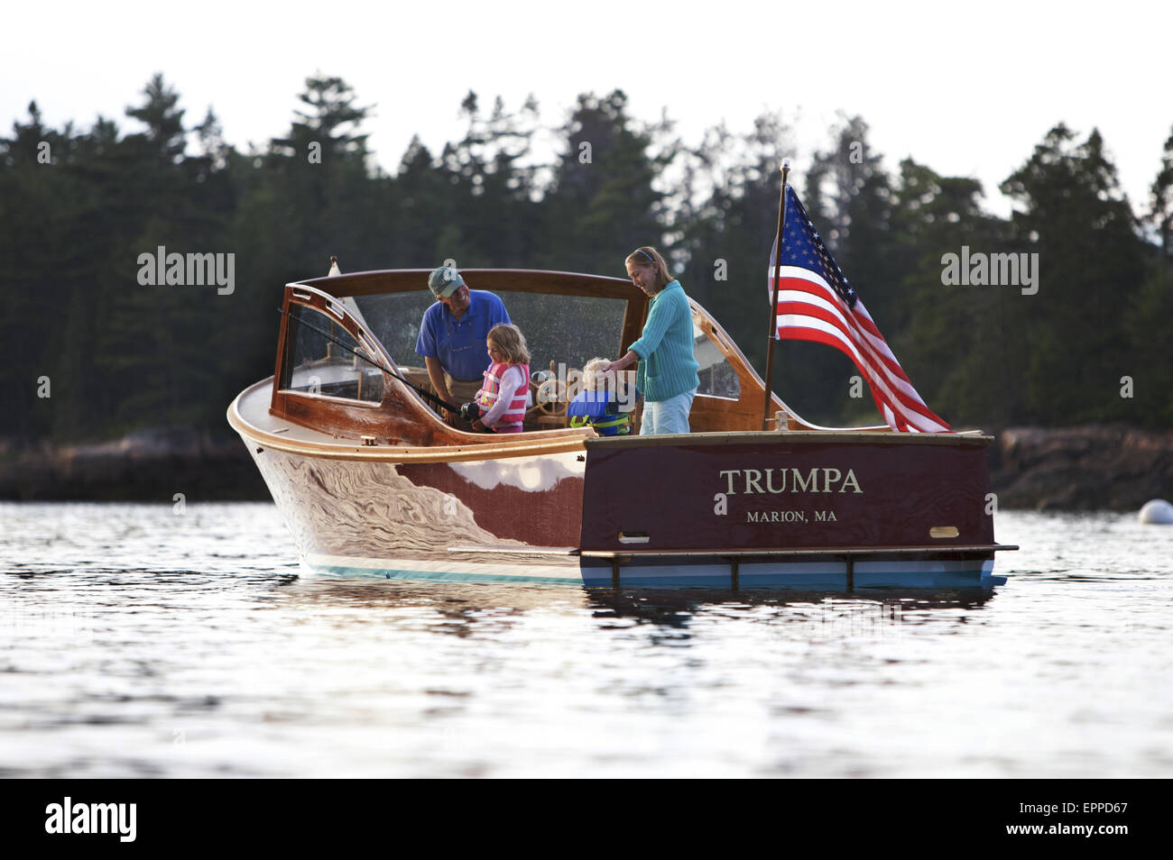 Senior man drives a power yacht in Somes Sound, Maine. - Stock Image