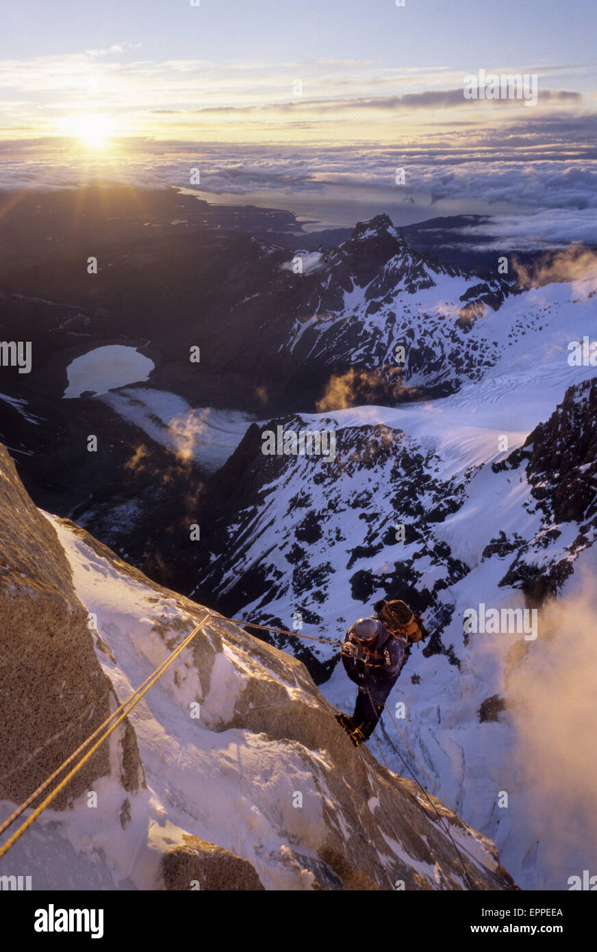 A climber rappels down Cerro Torre's south east ridge at dawn, after an ascent of that peak, in Argentine Patagonia Stock Photo