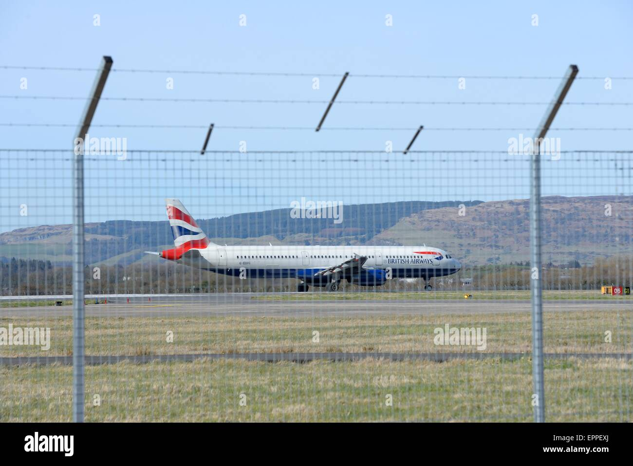 A British Airways plane prepares for take off viewed from behind security fence at Glasgow International airport, - Stock Image