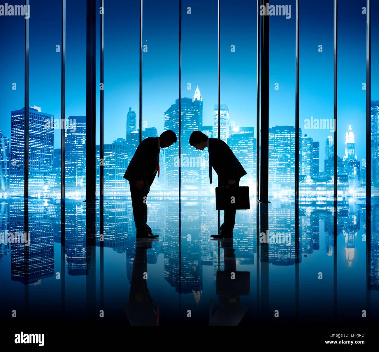 Two businessmen bowing to each other in an office building. - Stock Image