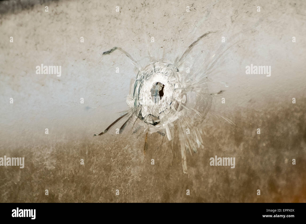 Bullet hole left in a window after a gun attack on a house - Stock Image