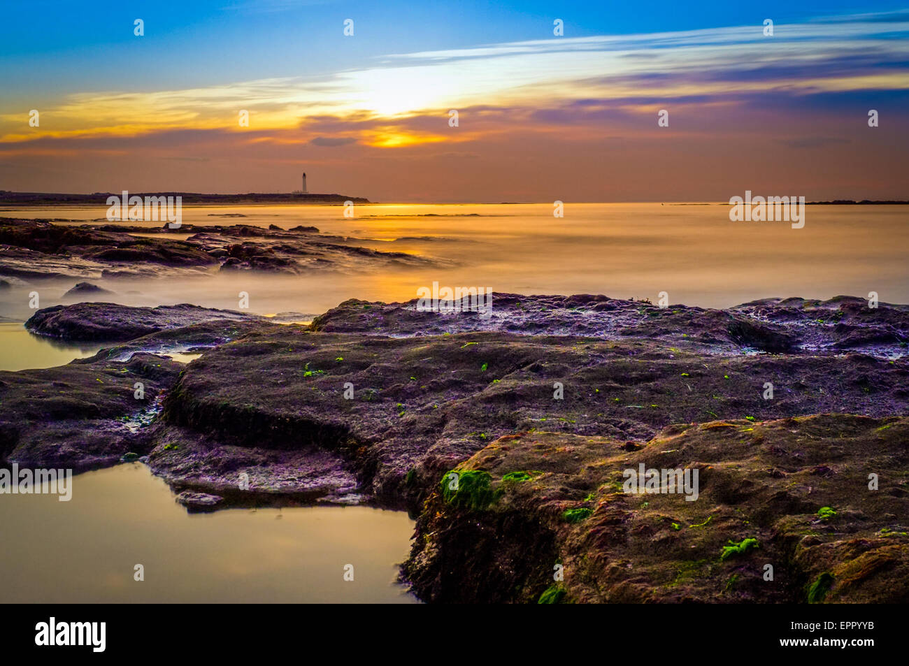 Lossiemouth lighthouse at sunset.  High Tide. - Stock Image
