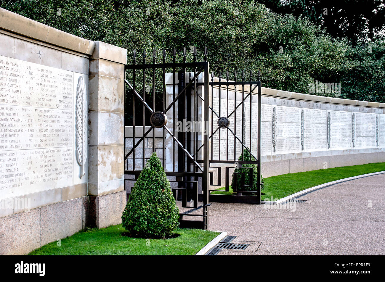 Wall in the peaceful but poignant gardens of American Cemetery, Omaha Beach, Normandy, France inscribed with names - Stock Image