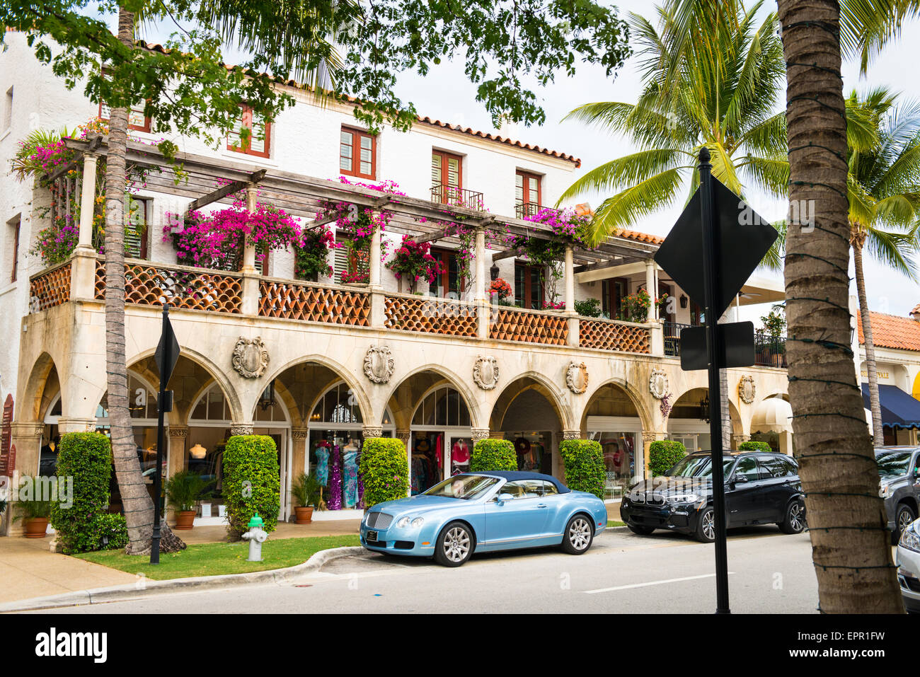 Florida Palm Beach Worth Avenue luxury shopping street road colonial style arcade colonnade fancy cars Bentley BMW - Stock Image