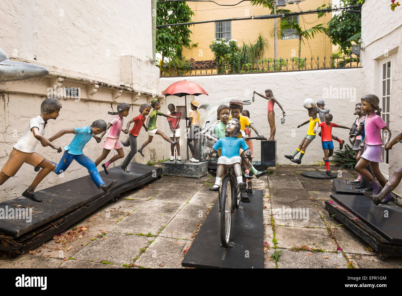 Florida Palm Beach Worth Avenue art work child children figures at play fun playing bicycle by artist Prince Monyo Stock Photo