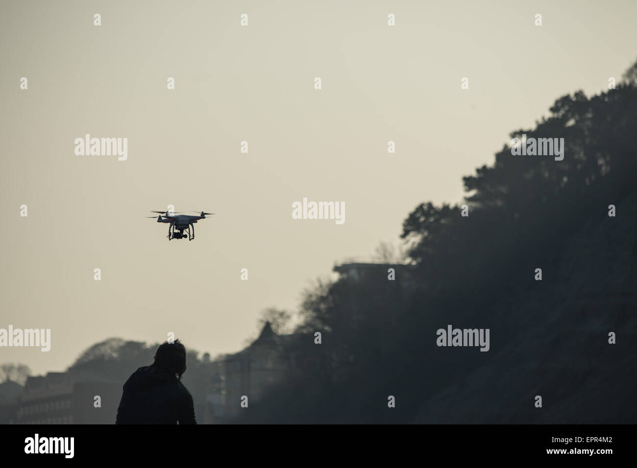Silhouette of man flying drone over cliffs at the sunset - Stock Image