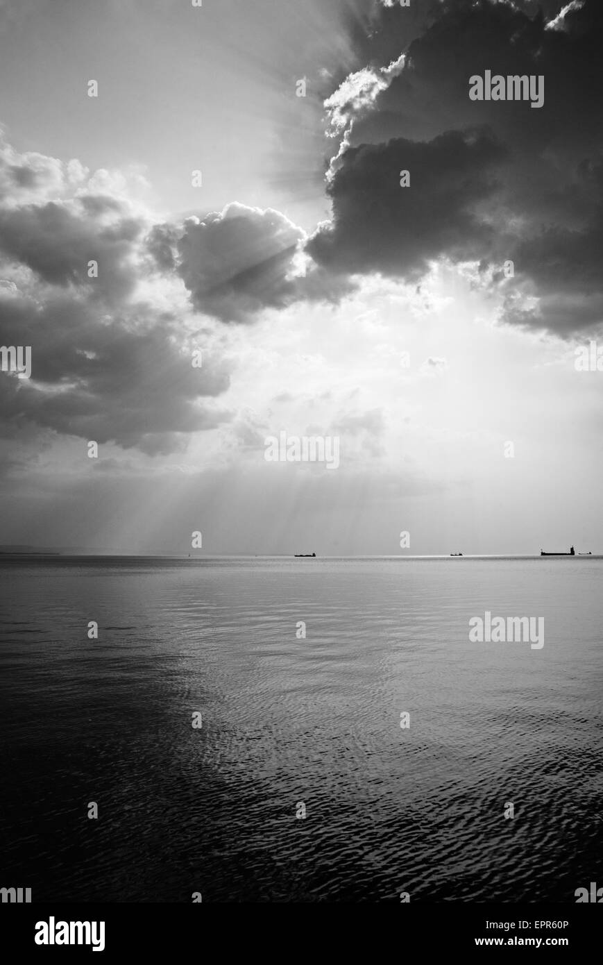 Scattered clouds produce beautiful rays of sunlight over the ships entering and leaving trieste Bay, Italy. - Stock Image