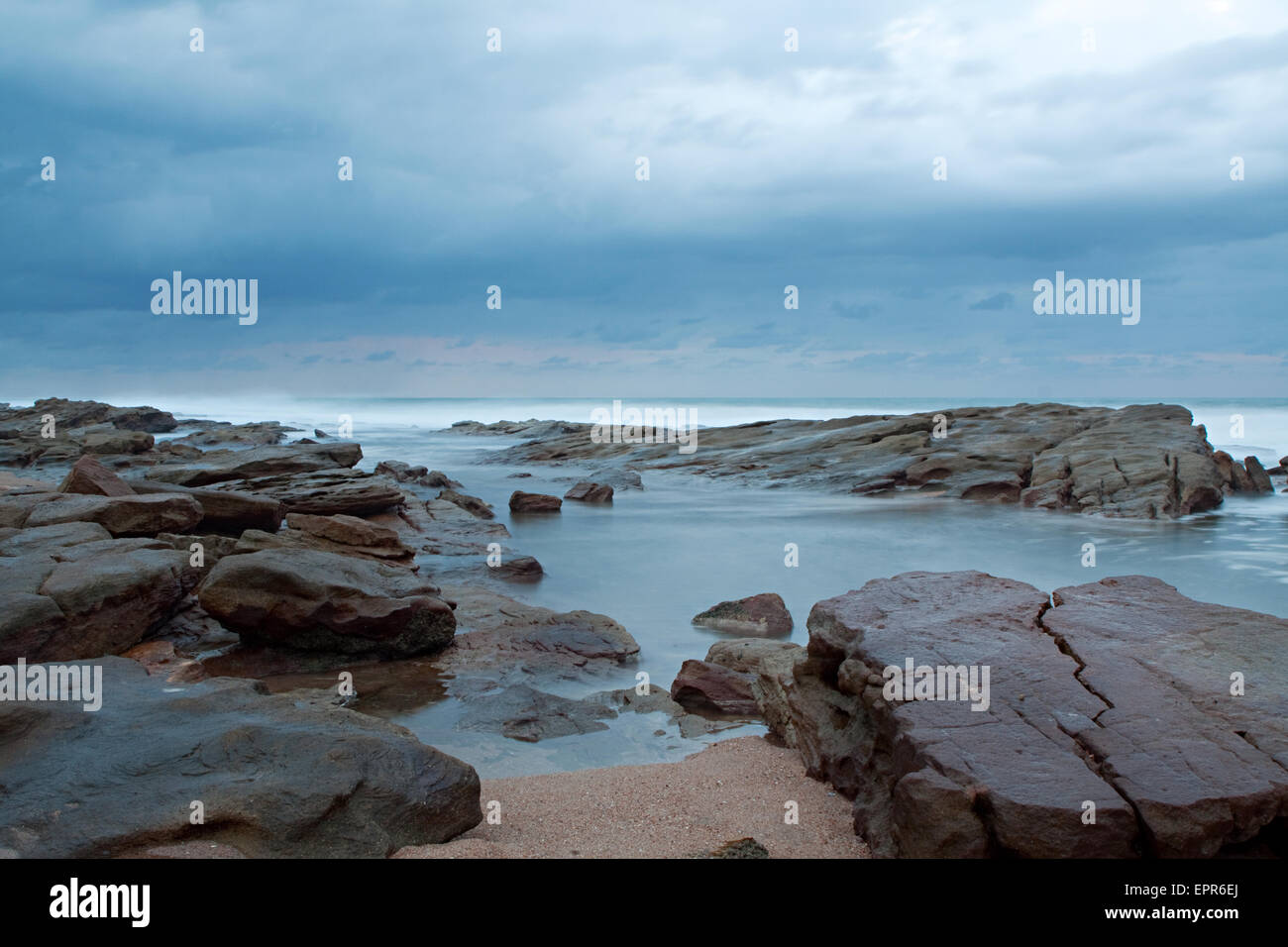 sea rockpool on stormy overcast day - Stock Image