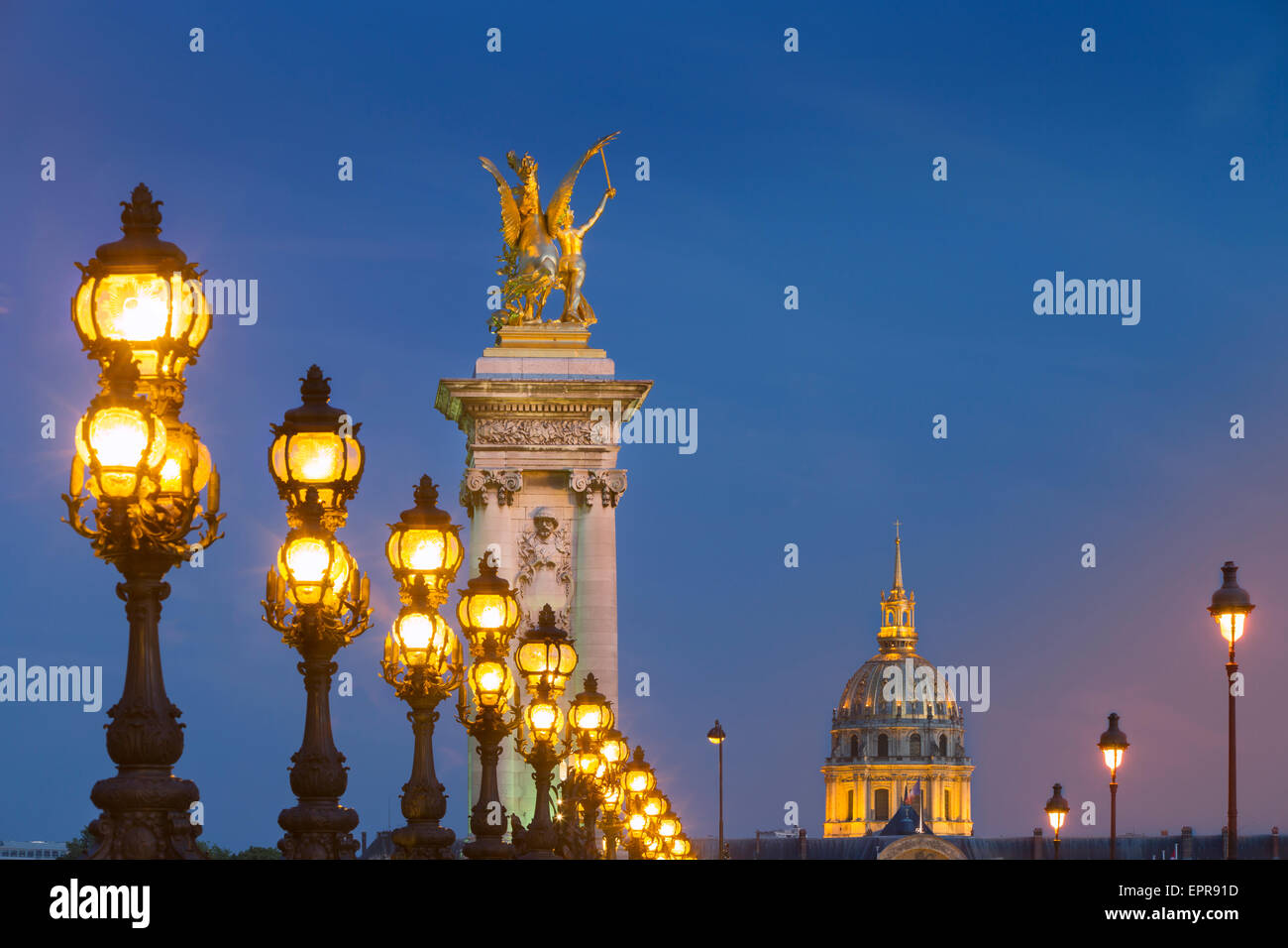 Row of lampposts along Pont Alexandre III with dome of Hotel des Invalides beyond, Paris, France Stock Photo