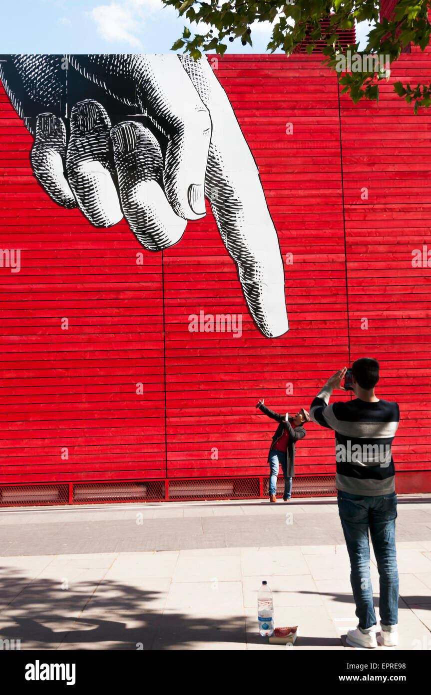 People posing and photographing in front of a large finger advertising the production of Everyman at the National - Stock Image