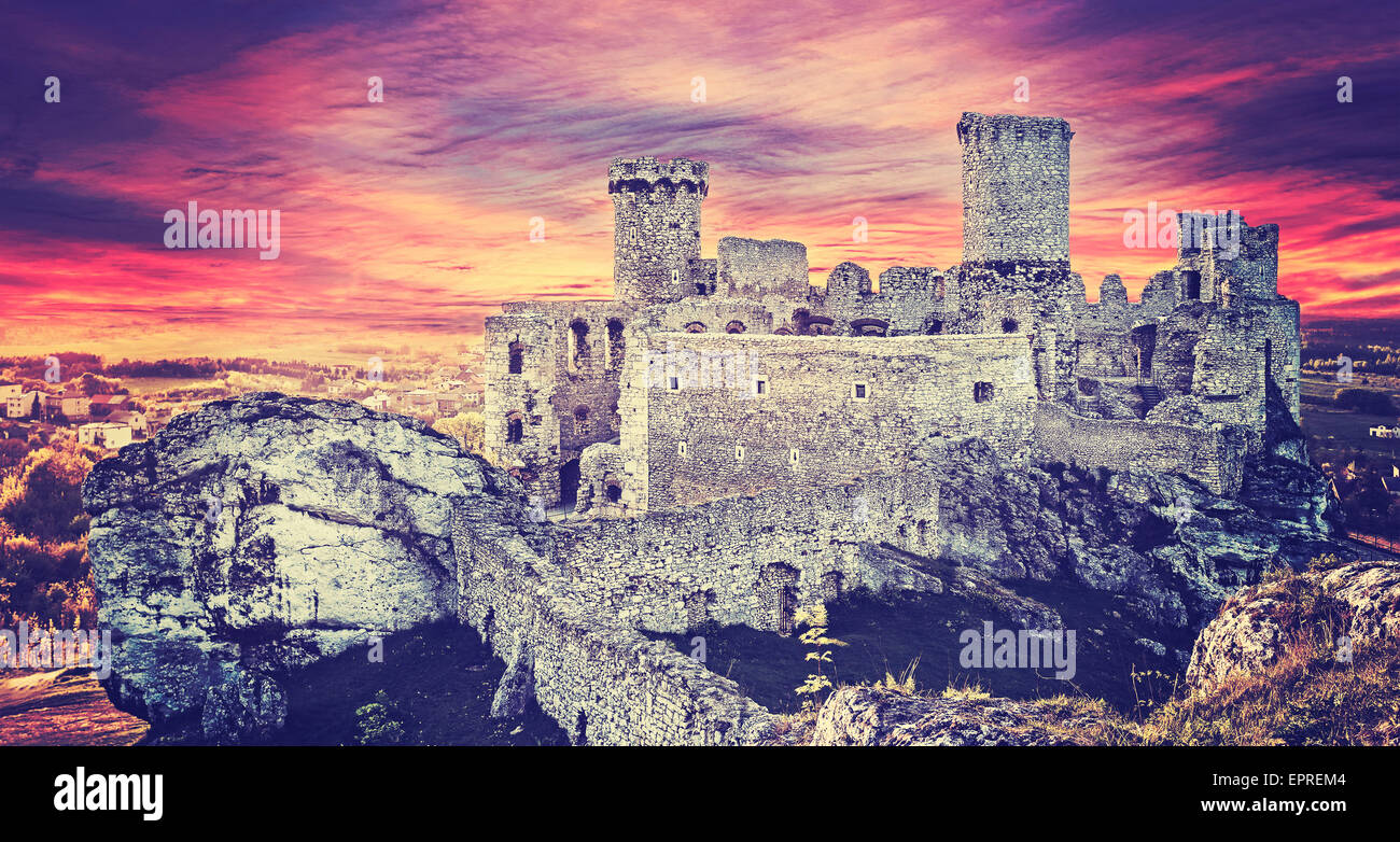 Vintage toned picture of a dramatic sunset over Ogrodzieniec castle ruins, Poland. - Stock Image