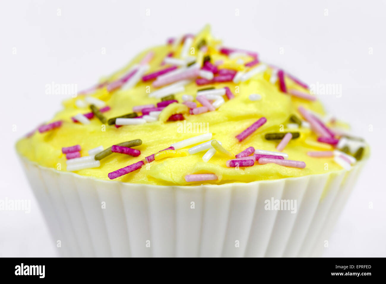 Pretty colourfully decorated cupcake or fairy cake with yellow icing and coloured sprinkles on a white background - Stock Image