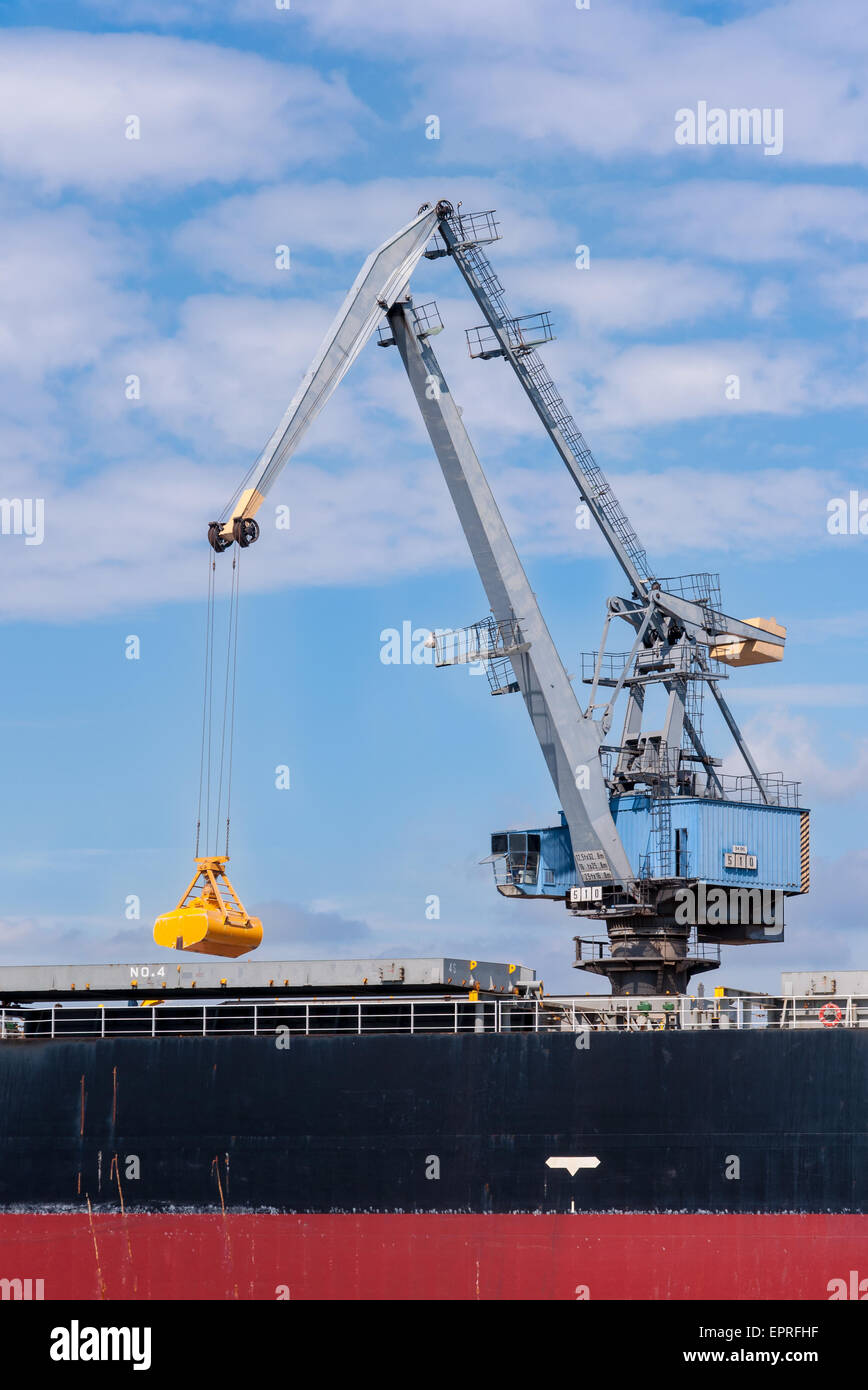 Port crane in Gdansk, Poland, with the closed grabbing bucket loading / unloading the ship - Stock Image