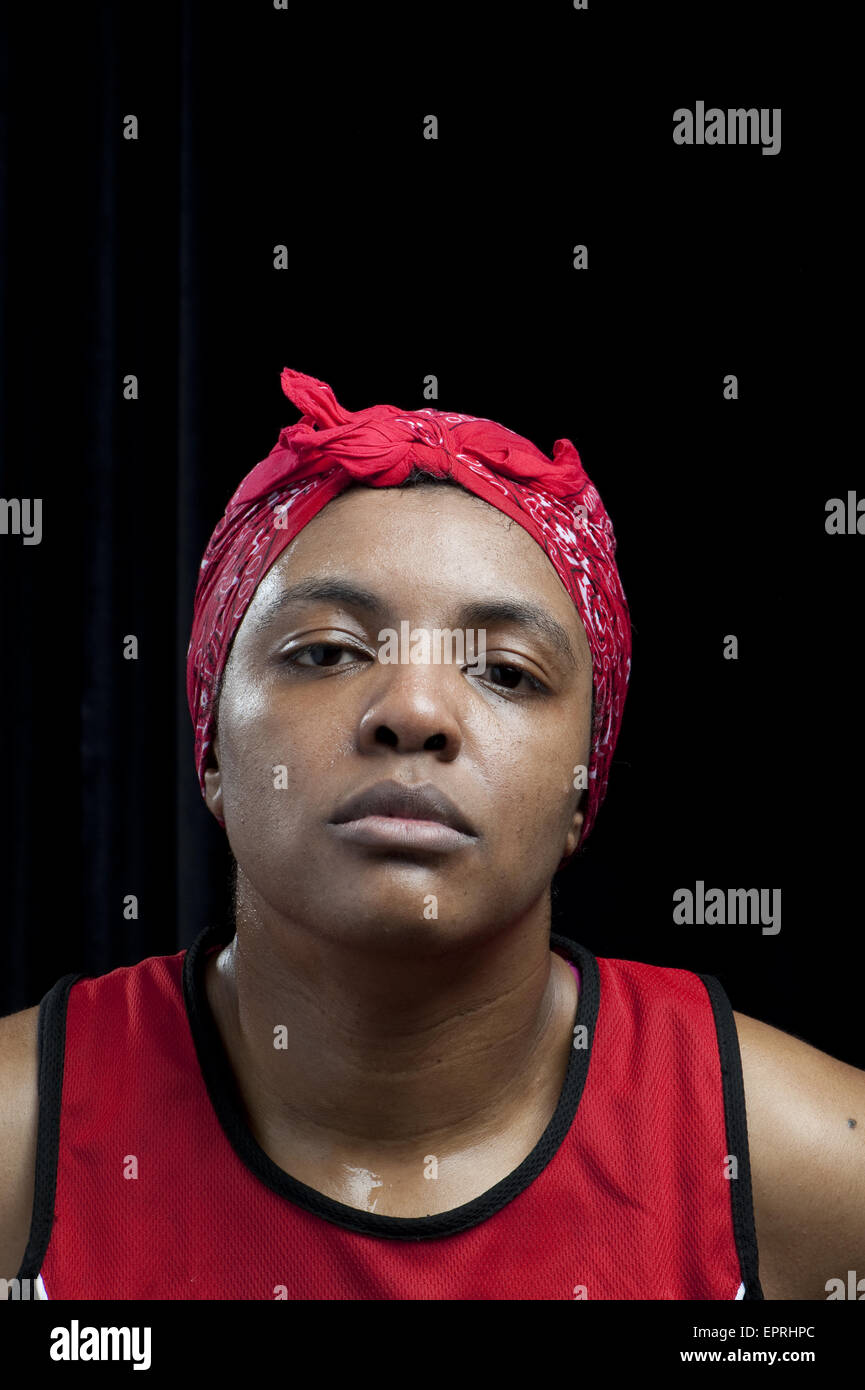 A female boxer wearing a headband stares deadpan after winning her semi-final round stands in a portrait at the - Stock Image