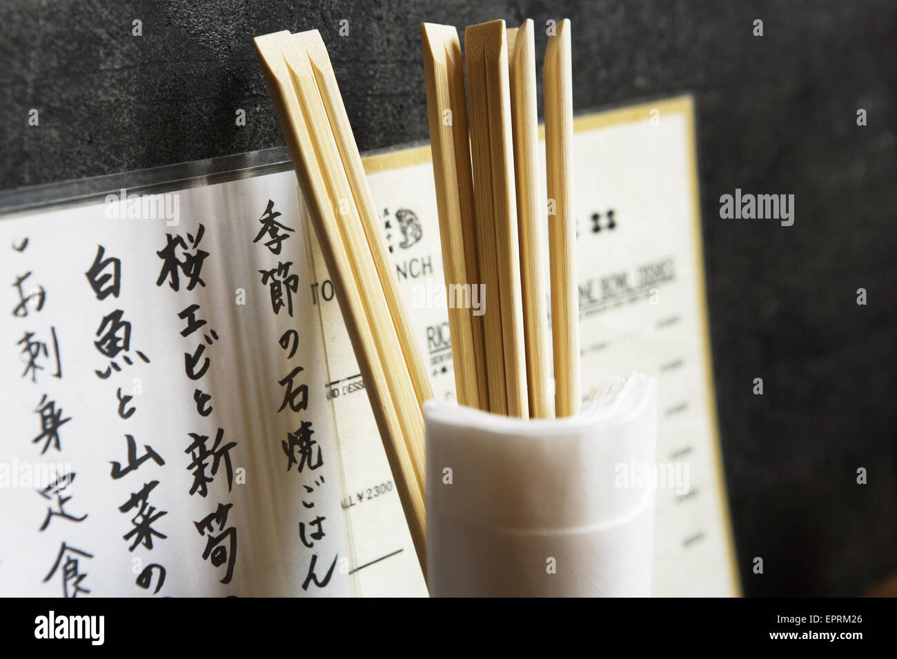 Restaurant menu, chopsticks in glass with napkins against wall, Tokyo, Japan. - Stock Image
