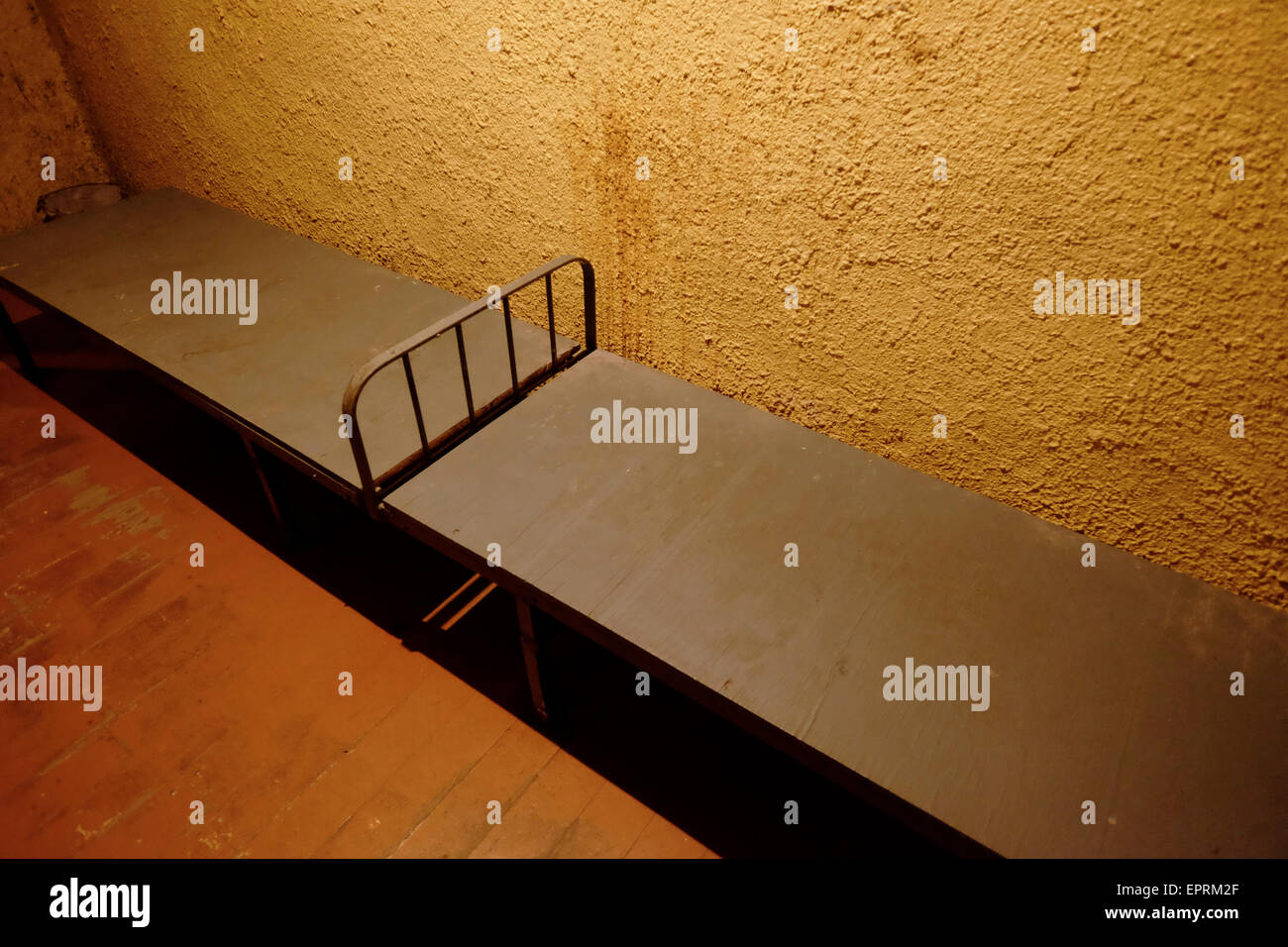 Prisoner beds inside a jail at the former KGB, or 'Cheka' headquarters known by locals as the Corner House in Riga - Stock Image