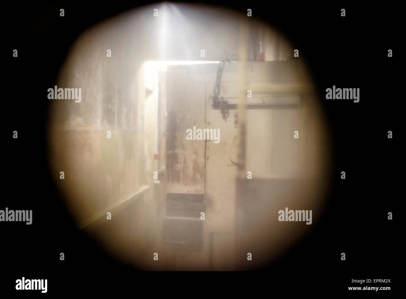 View of basement prison cells through a cell  peephole at the former KGB, or 'Cheka' headquarters known by locals - Stock Image